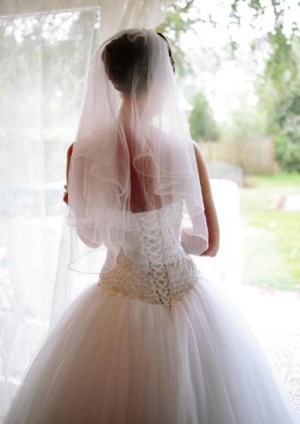 Hochzeitsfotograf Bremen Oldenburg - Braut steht am Fentser und schaut heraus