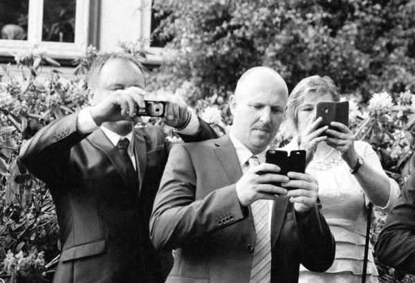 Hochzeitsfotograf Bremen - Hochzeitsgäste mit ihren Smartphones
