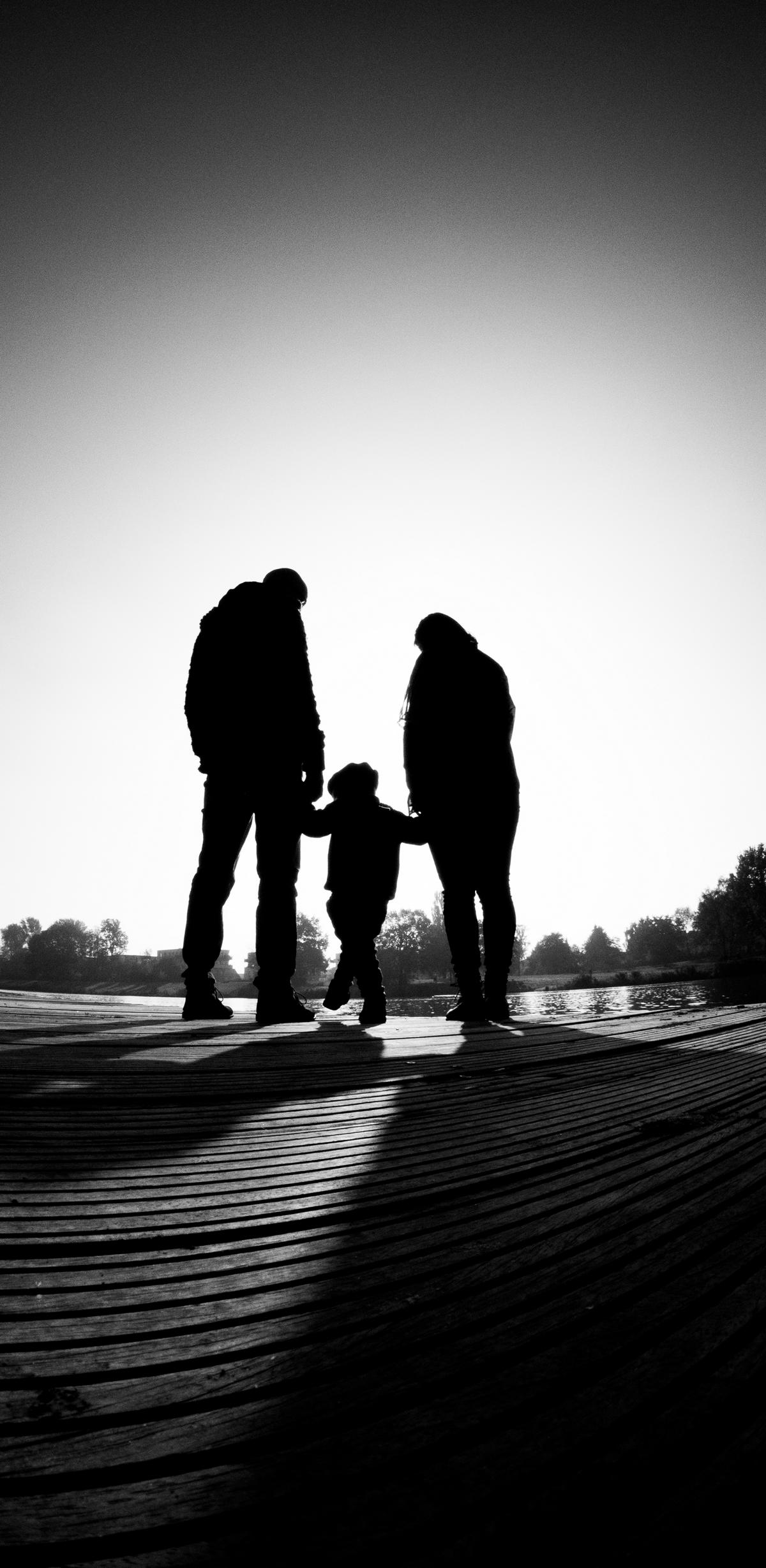 Eltern und Kind stehen am Wasser