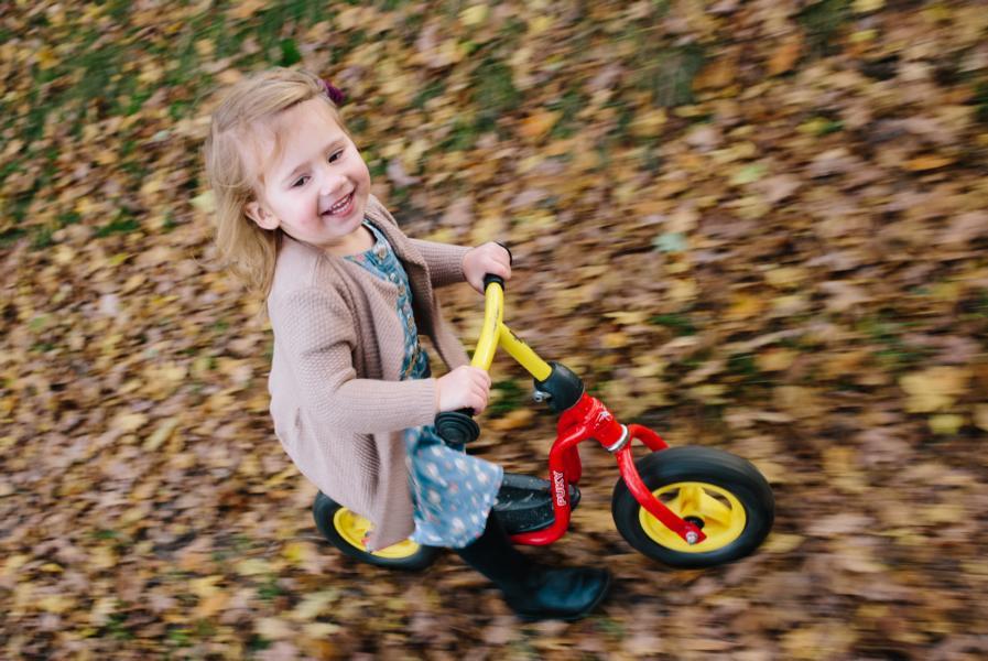 Mädchen fährt mit Fahrrad durch das Laub